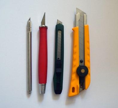 Zwei Skalpelle (links) in unterschiedlichen Größen für die Feinarbeit, ein einfacher Cutter (grün) für größere, gerade Schnitte und ein großer Cutter (gelb) für schwere Materialien wie Graupappe.